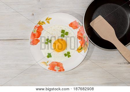 Fried eggs in a plate with a frying pan on a wooden background