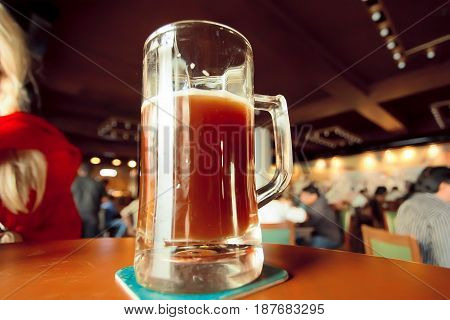 Craft beer mug on bar table of huge space with drinkers and eaters