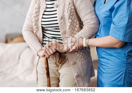 Sunset years. Admirable neat medical worker making sure elderly lady standing firm while she trying taking a little walk at home