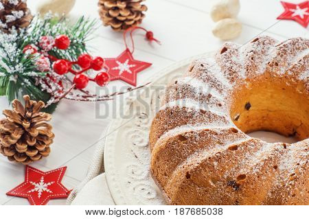 Traditional Xmas bundt cake with raisins dried cherries cranberry and sugar powder on a white plate. Ring cake with Christmas stars on white wooden table close-up. Festive table setting.