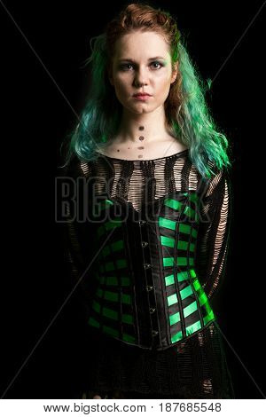 Woman in cosplay corset posing in studio with a green light from behind. Studio photo. Fashion and cosplay