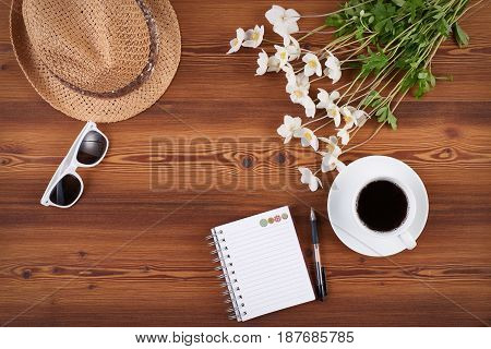 Top view of spring set of straw hat, sunglasses, white romantic anemone flowers and notebook with blank copy space for text on wooden background