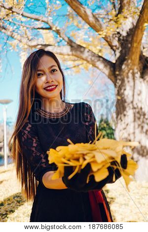 Beautiful girl in black vintage dress and hand glove. Woman in retro dress playing in the park with ginko leafs. Red lips