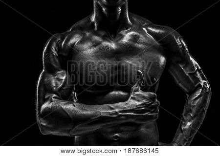 Part of a man's body on a dark background with copyspace. Studio shot on black background. Black and white, b w
