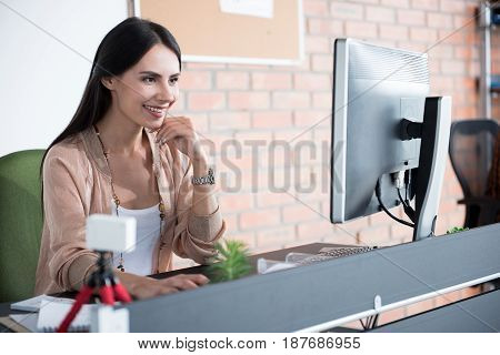 Happy female worker is sitting near desk and glancing at screen of computer. She working with smile