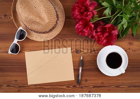 Top view craft envelope with blank copy space for text, straw hat, sunglasses and cup of coffee on wooden background