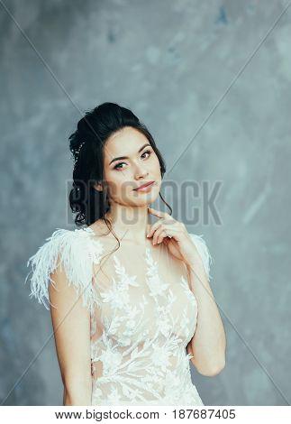 Bride brunette in wedding dress posing on grey background