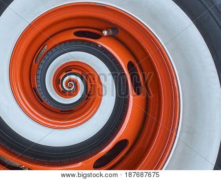 Car automobile wheel rim tire spiral abstract fractal background. Orange wheel rim spiral effect pattern abstract background. Automotive abstract wheel. Incredible orange white car wheel rim