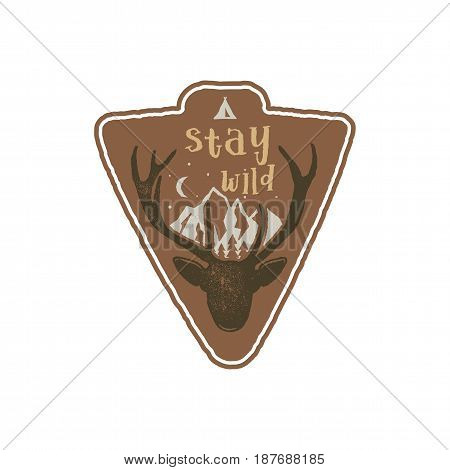 Hand drawn vintage camping badge and hiking label with wild animals design elements. Included deer head, mountains and quote text- stay wild . Old style patch. Rustic stamp template.