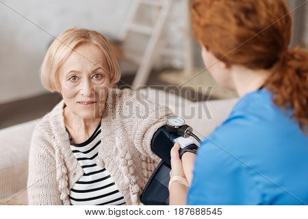 Diagnostics at home. Precise professional medical worker employing special equipment for conducting diagnostics and checking patients blood pressure