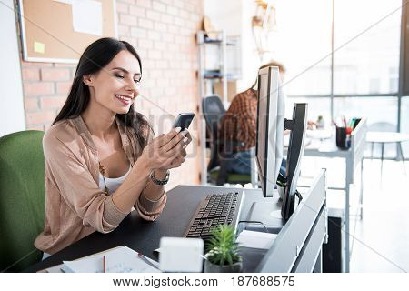 Happy woman is typing on phone. She sitting near workplace with smile. Her colleague absorbedly working