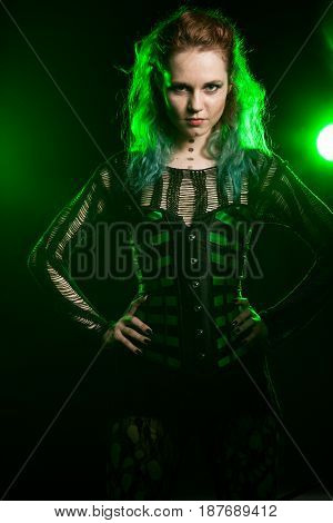 Cosplay model posing in corset in studio photo with a green light from behind. Studio photo. Fashion and cosplay