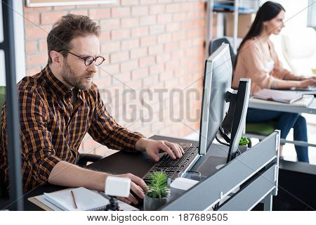 Concentrated office worker is using computer. He sitting near table and typing on keyboard. Female colleague doing her job