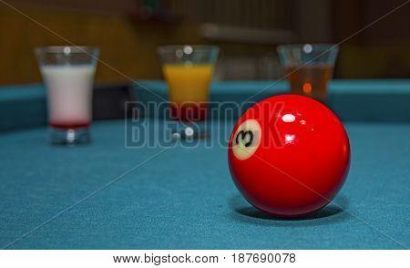 on a billiard table stand with coloured glasses of alcohol. Billiards, balls and stack