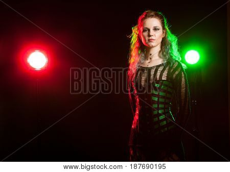 Sexy cosplay model in corset in studio photo with a red and green light from behind. Cosplay and subculture