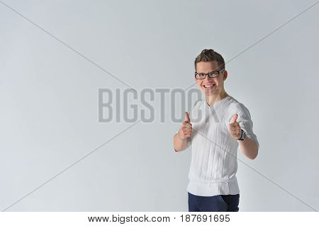 Portrait of a smiling casual spectacled man showing two thumbs up and looking at camera over gray background. Man looking at camera. Positive human emotion facial expressions, symbol