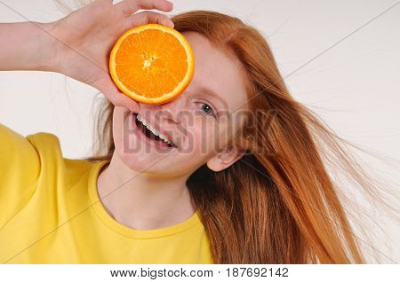 Teenage red hair girl holding piece of orange in front of her eye while standing against white background. Great food for a healthy lifestyle