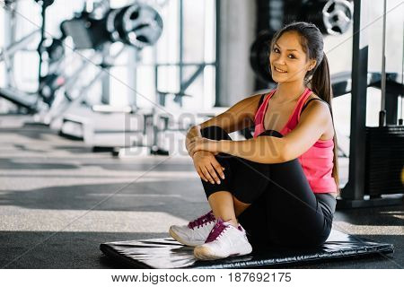Indoors shot of beautiful girl resting after fitness training. tired young girl sitting break after exercising in gym