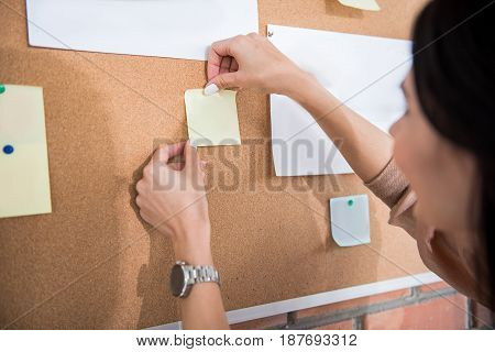 Female manager is attaching sticker at special board for advert. focus on female hands