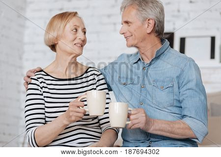 Hot feelings. Two elderly charismatic people spending some time together while sitting on bed and chatting with cups in their hands