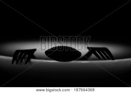 Spoon And Fork On Empty Plate In White Tone, Diet, Poverty Or Afraid Of Eating Concept