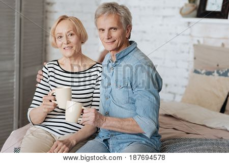 Inspiring couple. Adorable enthusiastic nice family having nice conversation while sharing a moment of unity and drinking tea