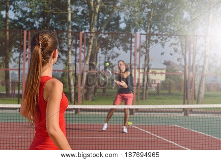 Woman playing tennis and preparing for sports competition. Women against men.Healthy fitness concept with active lifestyle.