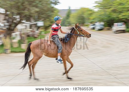 NIEU BETHESDA SOUTH AFRICA - MARCH 21 2017: An unidentified rider on a horse galloping through the streets of Nieu-Bethesda an historic village in the Eastern Cape Province
