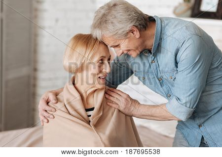 Full of love. Lovely charming senior people laughing together while the man fulfilling ladies favor and brining her a blanket