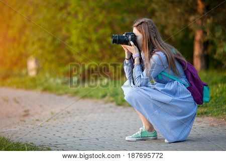Beautiful young girl taking pictures in the forest. The girl with the camera. Tourist. Sunset. Summer evening