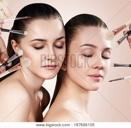 Cosmetics brushes doing make-up to young women. Over beige, background.