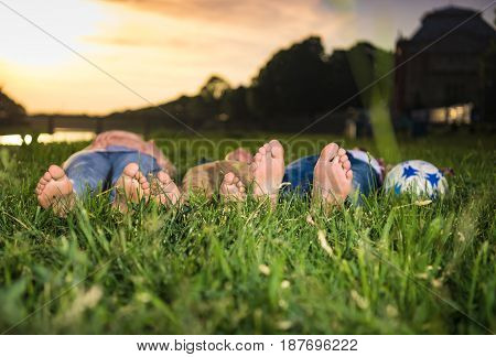 Group Of Happy Kids Lying On The Grass