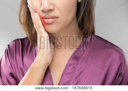 Suffering from toothache. Beautiful young woman touching her cheek standing against grey background. Dental health and care. People with teeth problem concept.