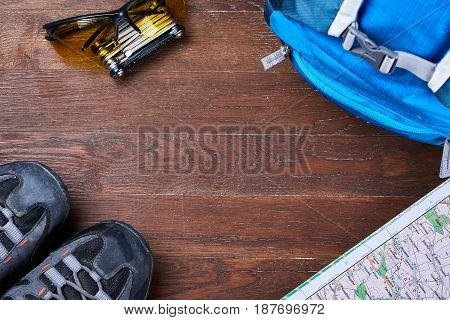 Top view of the set of equipment for travelling on brown wooden boards. Set for tourism: blue backpack, sportive shoes, map, sunglasses and gear for the bicycle. Planning and preparation for the trip. Concept of the active lifestyle.