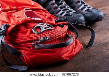 Hiking equipment: backpack and trekking boots on the wooden boards. Horizontal photo and brown background. Tourist backgrounds and still-life. Preparation and planning for the travelling. Concept of the active lifestyle.