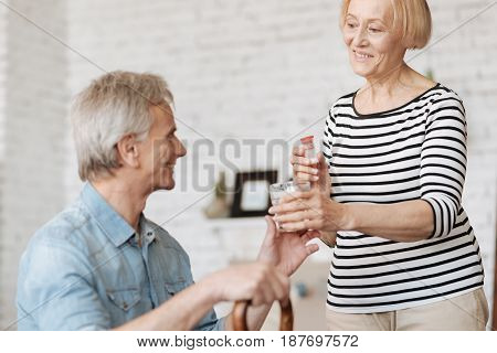 Ensuring recovery. Motivated charismatic mature lady taking care of her man by making sure he taking his medicine and serving him a glass of water