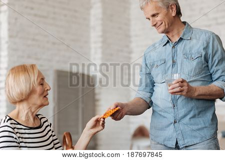 Time to get better. Admirable handsome aged gentleman giving his wife the pills she needing for recovering from recent disease