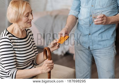 For our own sake, honey. Beautiful frail senior woman sitting on bed while her husband bringing her the medication and a glass of water for taking it