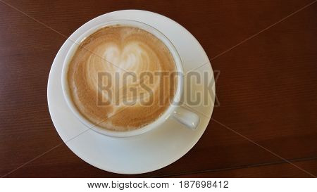 White cup with coffee and milk with drawings in form of heart on brown wooden background
