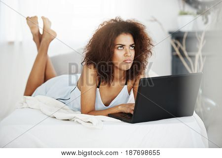 Upset sad young beautiful african girl in sleepwear lying with laptop on bed at home thinking.