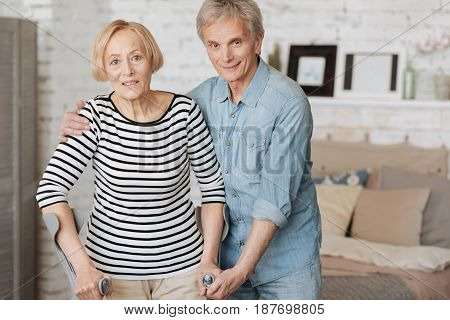 Always there for you. Tender motivated senior gentleman holding his wife for making sure she standing firmly while she trying taking a little walk