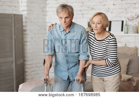 I got your back. Productive motivated aged gentleman wanting taking a walk and using the crutches for this while his wife supporting him