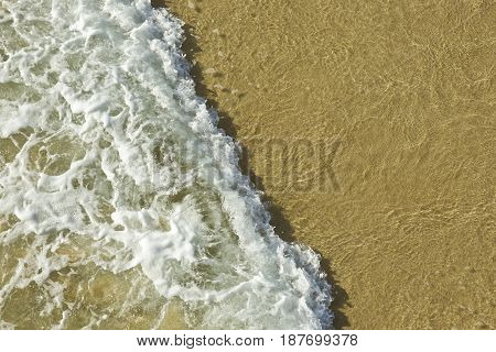 frothy breaking wave on a sandy beach on a summers day