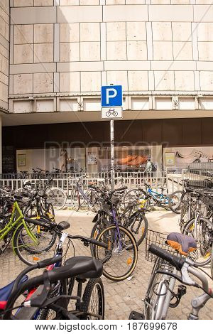 Regensburg,Germany-May 20,2017: Bicycles stand beneath a sign for a bicycle parking lot