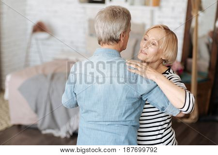 Sweet melody of emotions. Graceful loving senior lady dancing with her man and looking dreamy while enjoying her time with him
