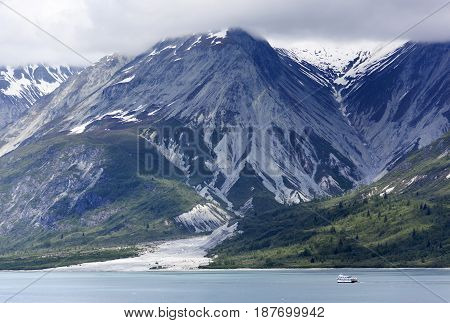 The small tourist boat passing by in Glacier Bay national park (Alaska).