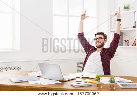 Happy successful businessman win, celebrate in office, sitting at workplace. Man in eye glasses, job in internet.