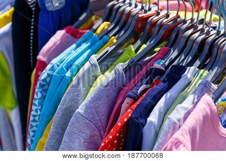 Baby clothes pants t-shirts sweaters shirts hanging on hangers in a shop outside in sunny weather