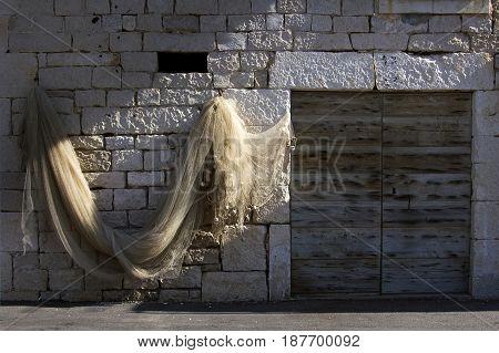 Drying fisherman's net on the old stone facade near wooden door in Povlja Brac Island Croatia
