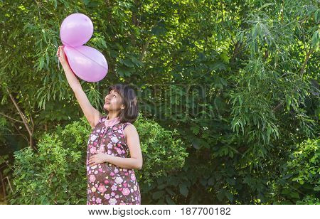 Pregnant woman with colorful balloons in the summer park.